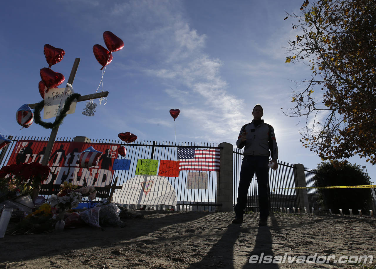 A man pays his respects at a makeshift memorial on Saturday, Dec.