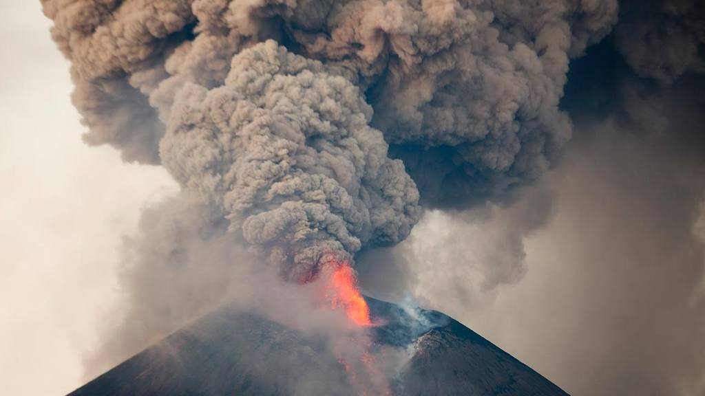The Momotombo volcano spews  a plume of gas and ash as well as glowin