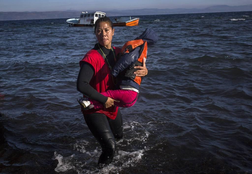 Una voluntaria ayuda a un niño a su llegada con otros refugiados a la isla griega de Lesbos.