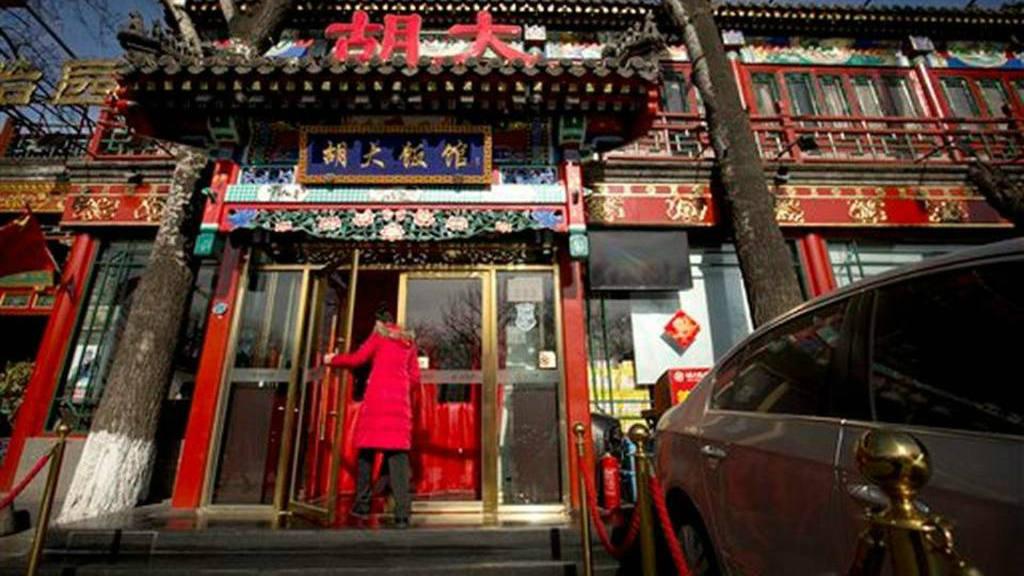 Una recepcionista entra a un local de la cadena de restaurantes Hu Da de Beijing