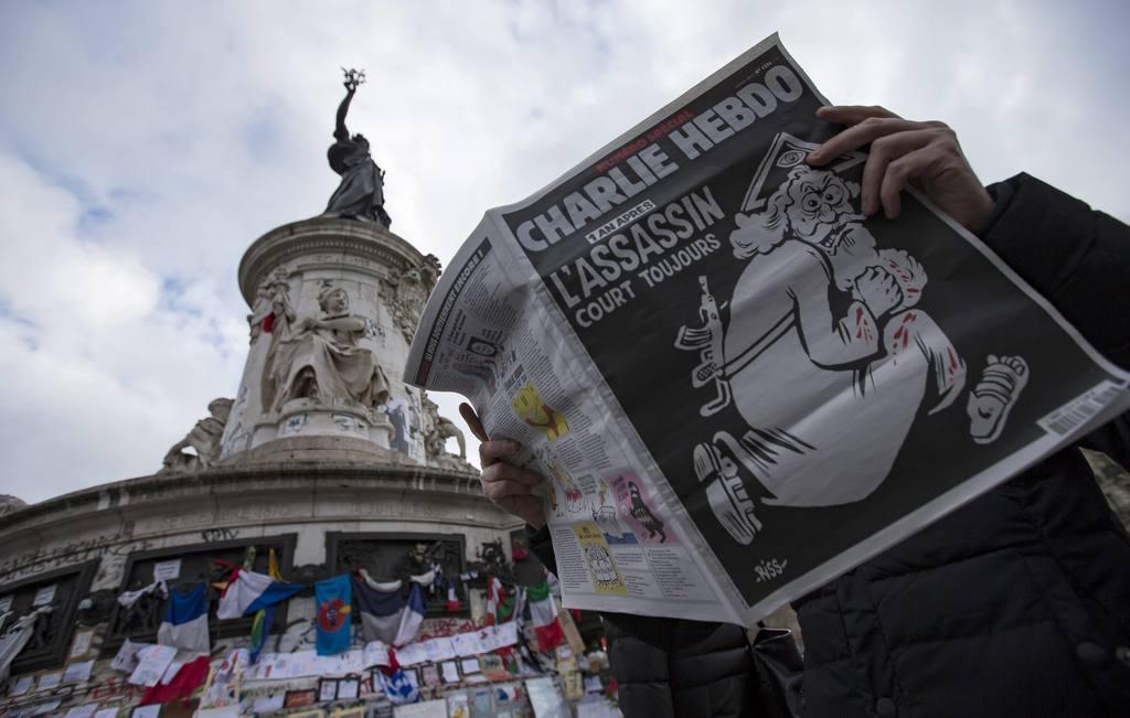 """Un hombre ojea el número especial publicado por el semanario satírico """"Charlie Hebdo"""" con motivo del primer aniversario del atentado yihadista contra su redacción."""