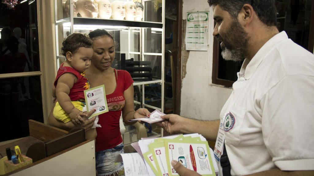 Una mujer recibe volantes informativos en el marco de una campaña contra el mosquito Aedes aegypti.