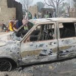 Niños se reúnen alrededor de un coche quemado tras un ataque de Boko Haram en el pueblo Dalori.
