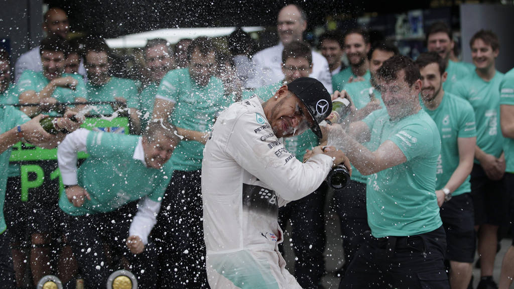 Mercedes driver Lewis Hamilton of Britain is celebrated by tem member