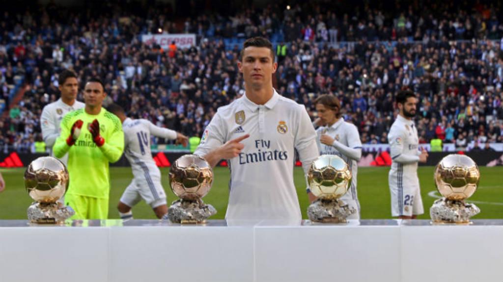 Cristiano Ronaldo junto a sus cuatro Balones de Oro en el césped del Santiago Bernabéu.