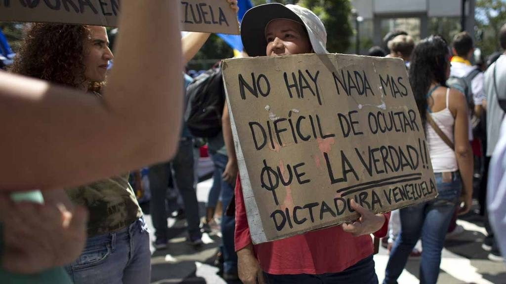 "A protester holds a sign with a message that reads in Spanish: ""There"