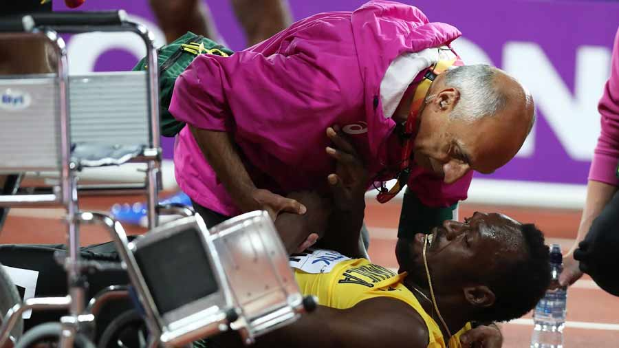 MEdical staff attends to Jamaica's Usain Bolt who hurt himself during