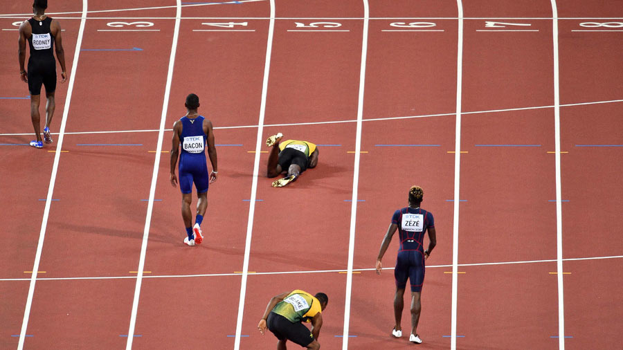 Jamaica's Usain Bolt (C front) lies on the track after pulling up inj