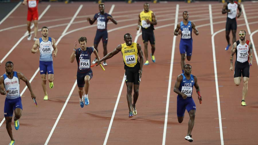 Jamaica's Usain Bolt (C) pulls up injured in the final of the men's 4