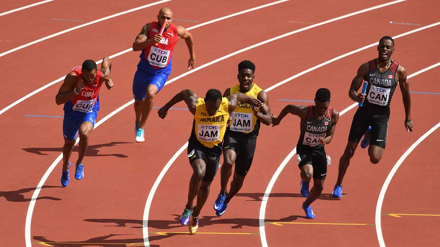 Jamaica's Usain Bolt (C) takes the baton from team-mate Michael Campb