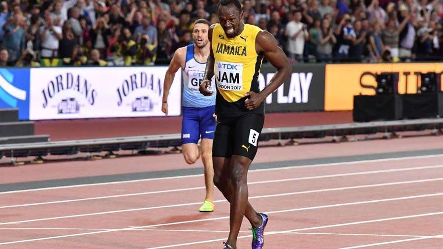 Jamaica's Usain Bolt limps after pulling up injured in the final of t