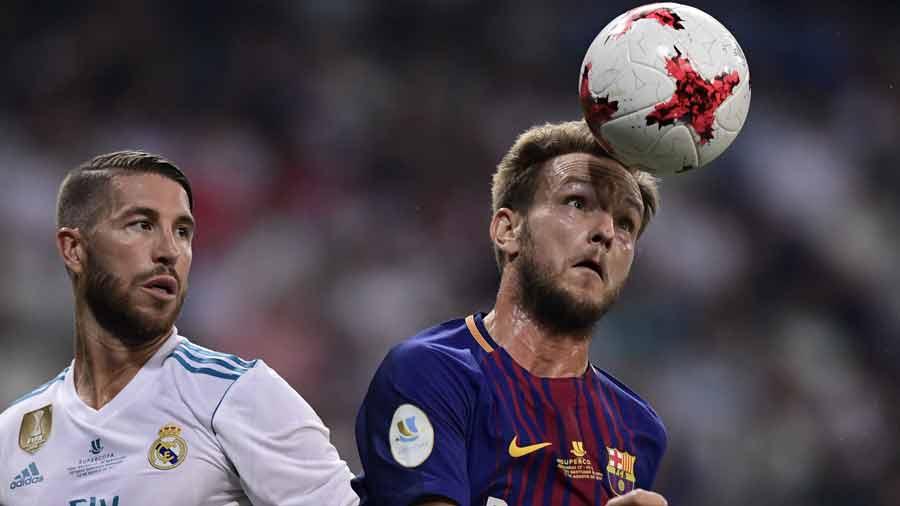 El centrocampista croata del Barcelona Ivan Rakitic lidera el balón ante el defensa del Real Madrid Sergio Ramos