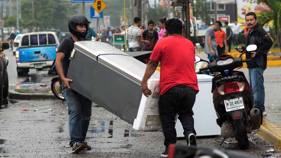 Men carry a refrigerator looted from a shop as supporters of Honduran