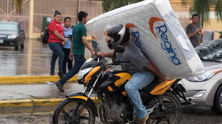 A man carries a matress looted from a shop as supporters of Honduran