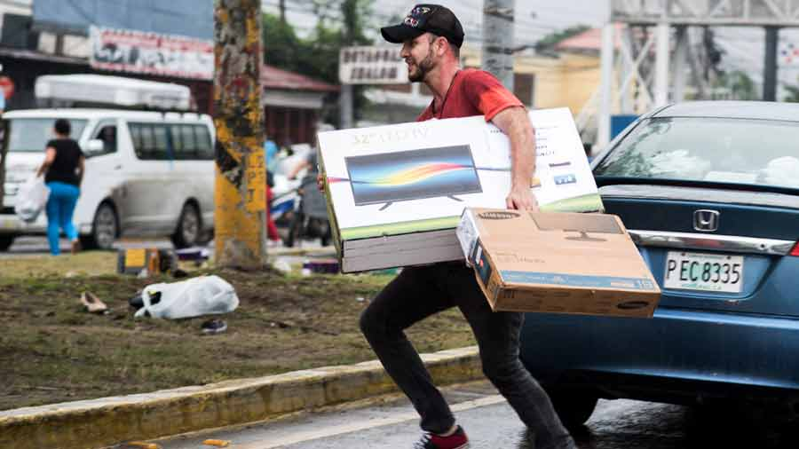 A man carries TV sets looted from a shop as supporters of Honduran pr