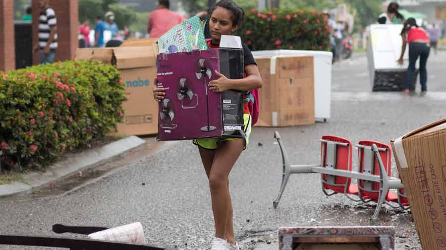 A woman carries a fan looted from a shop as supporters of Honduran pr
