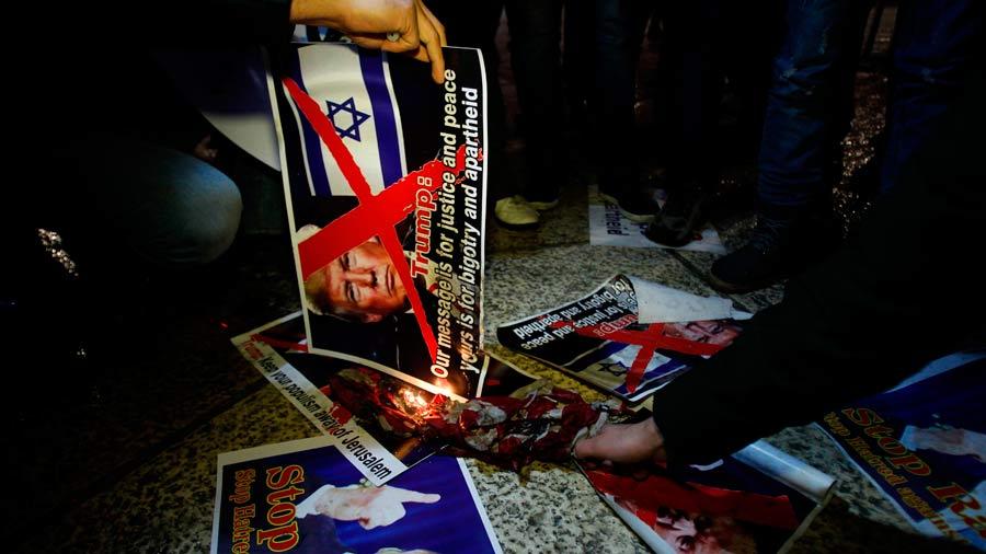 Palestinian demonstrators burn posters of the US president in Bethleh