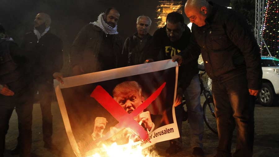 TOPSHOT - Palestinian protesters burn pictures of US President Donald