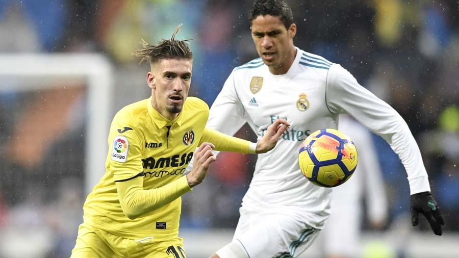 Real Madrid's French defender Raphael Varane (R) challenges Villarrea
