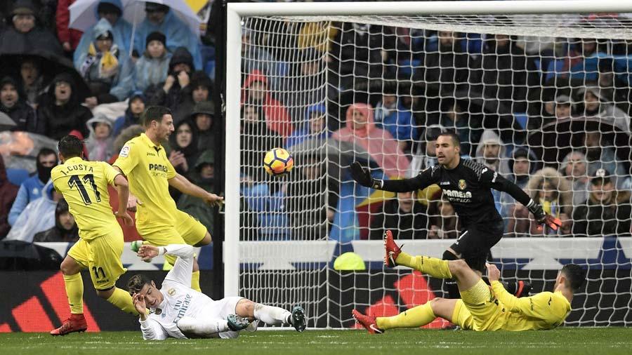 Villarreal's Spanish goalkeeper Sergio (R) prepares to block a shot o
