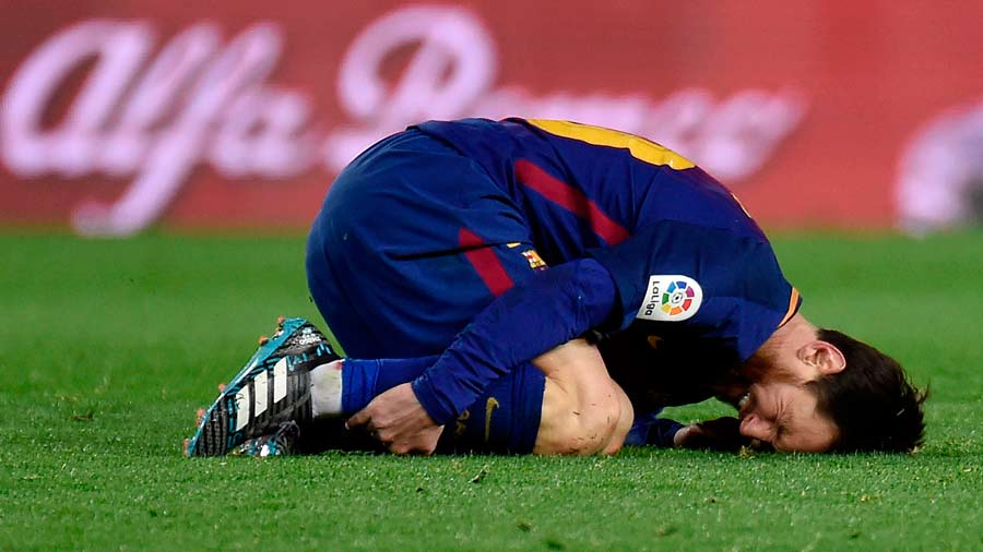 Barcelona's Argentinian forward Lionel Messi bends on the field after