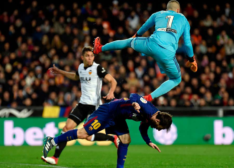 Valencia's Spanish goalkeeper Jaume (top) jumps over Barcelona's Arge