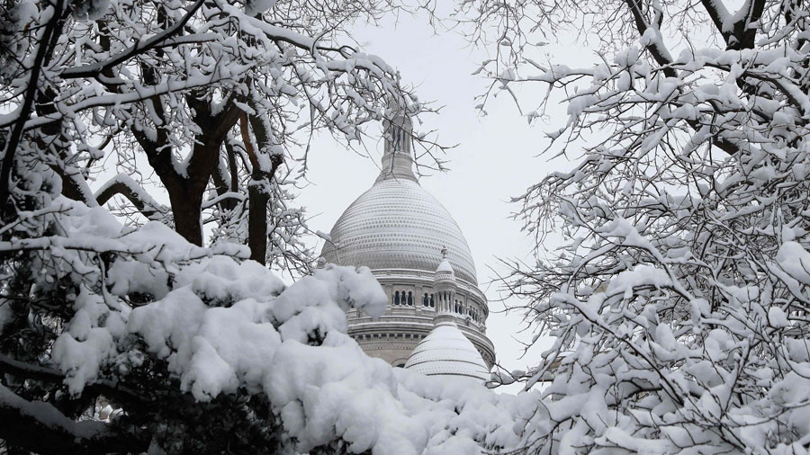 TOPSHOT - Snow covered trees are pictured near the Sacre Coeur basili