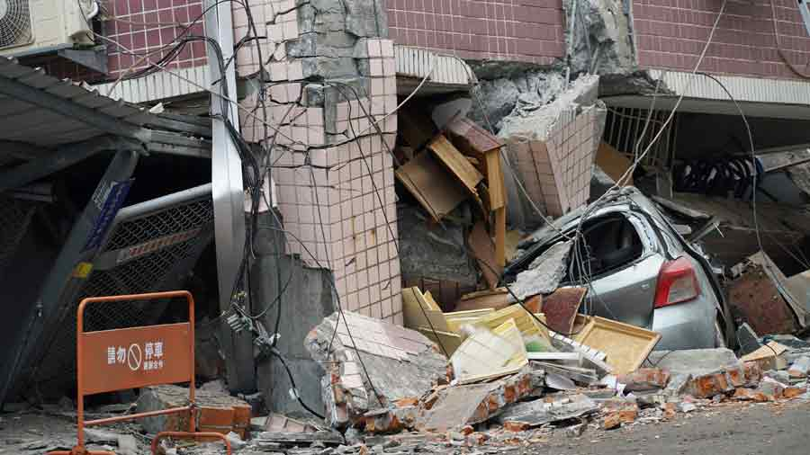 A car sits crushed by a building which came off its foundation after