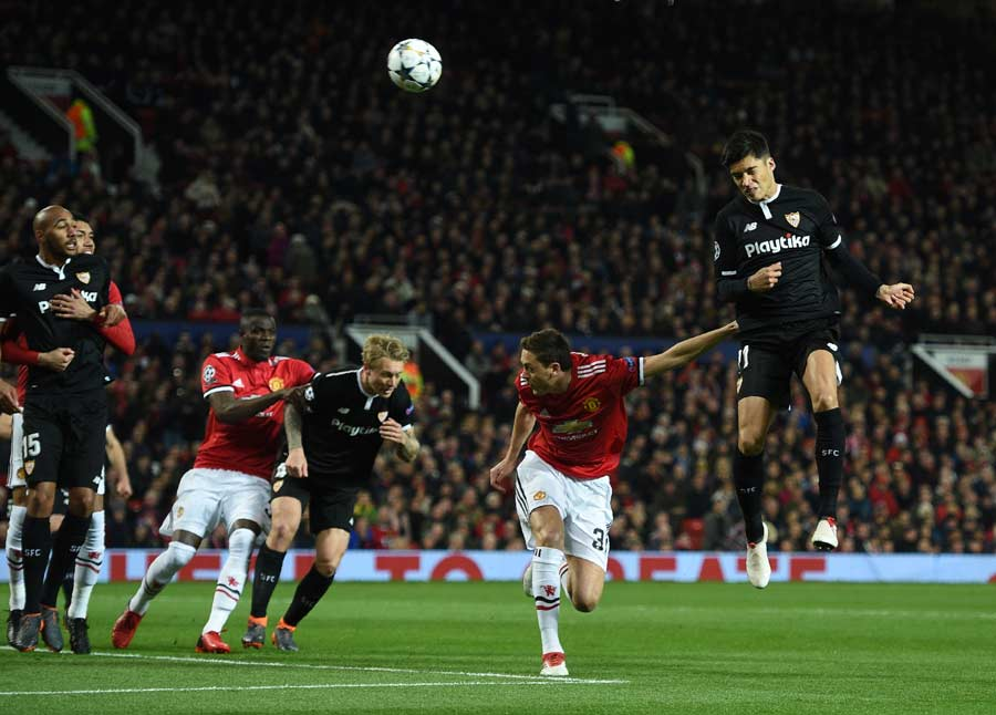 Sevilla's Argentinian midfielder Joaquin Correa (R) heads the ball pa