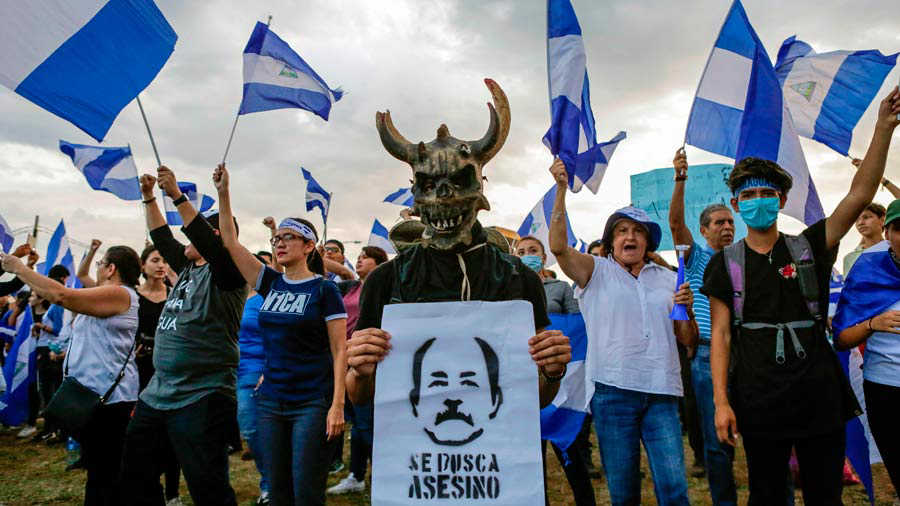 TOPSHOT - A student holds a sign depicting Nicaraguan President Danie