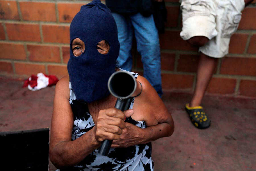 An hooded elderly woman holds a hand-made mortar during anti-governme