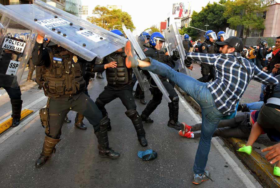 Teachers from across Mexico clash with police during a protest agains