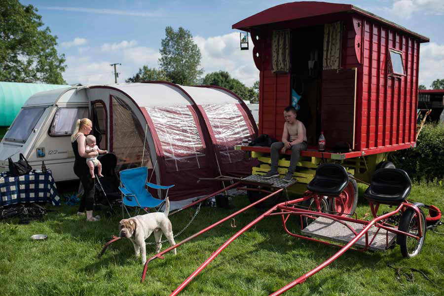 People sit outside traditional gypsy caravans on the opening day of t