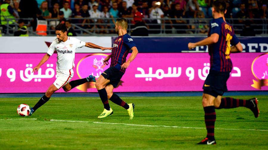 Sevilla's Spanish midfielder Jesus Navas (L) prepares to pass the bal