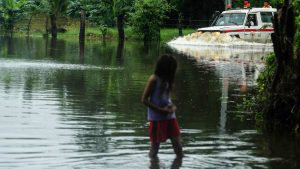 Salvadoran Red Cross ambulance passes down a flooded road due to heav