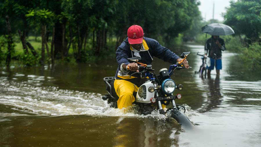 A man rides his motorcycle along a flooded road due to heavy rains at