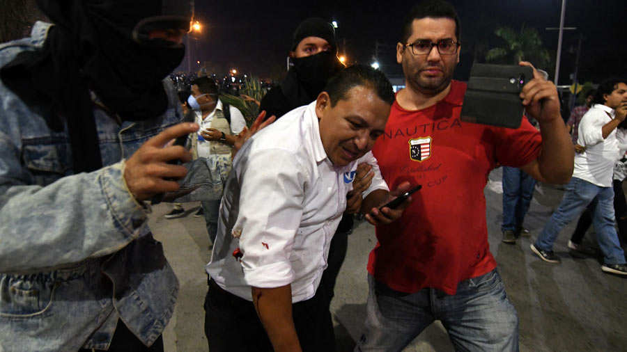 Honduran journalist Geovany Sierra of UNETV is helped by supporters o