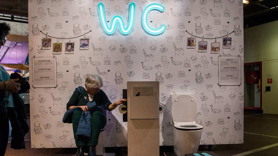 A woman sit on a toilet at the exhibition entitled