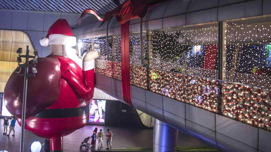 A large inflatable Santa Claus decorates the walkway facade of a mall