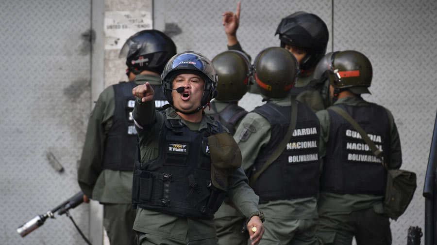 Members of the Bolivarian National Guard trough tear gas againts prot