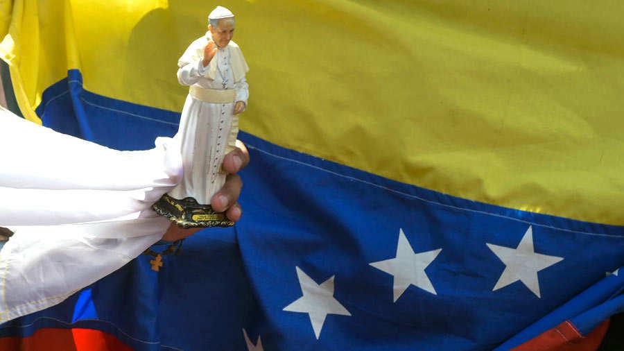 A faithful holds a souvenir doll of Pope Francis next to a Venezuelan