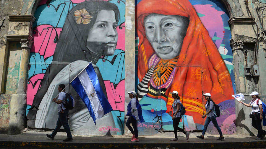A group of faithfuls with Nicaraguan national flags walk in Panama Ci