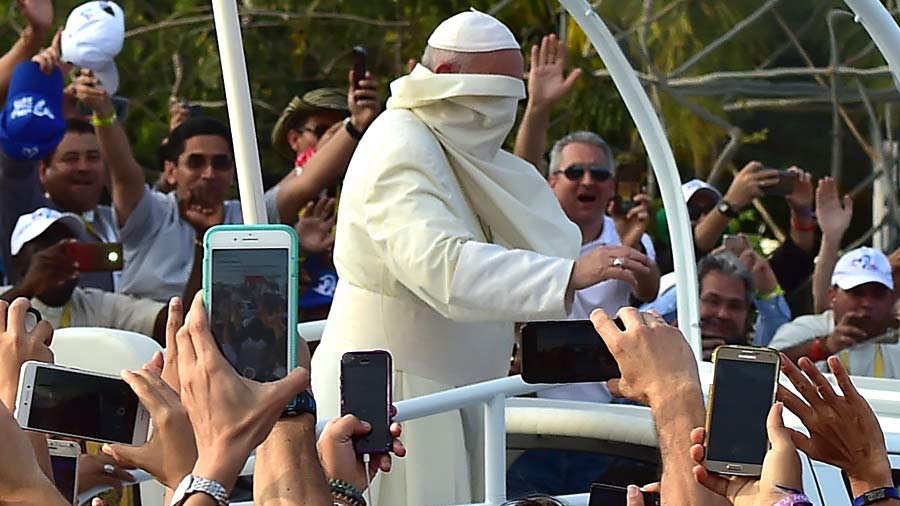 Pope Francis' cape sweeps in his face as he arrives for his welcome c