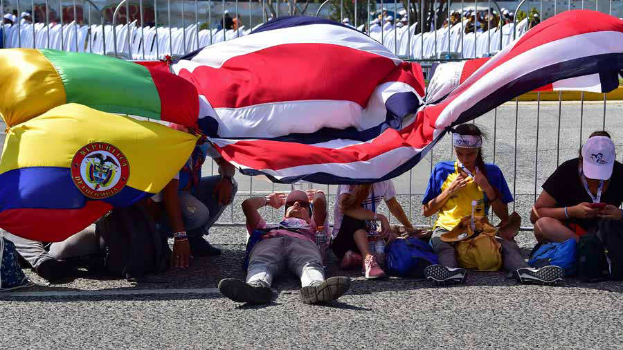 Pilgrims rest under flags as they wait for the arrival of Pope Franci