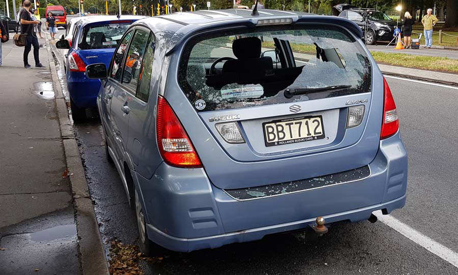 A car with shattered windows is parked close to the mosque after a gu