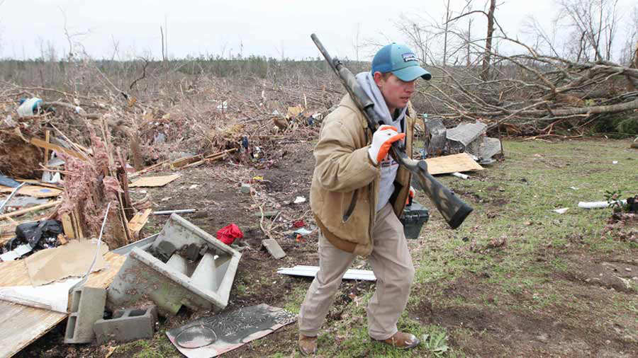 Joey Roush carries a rifle and other items from his mother's home aft