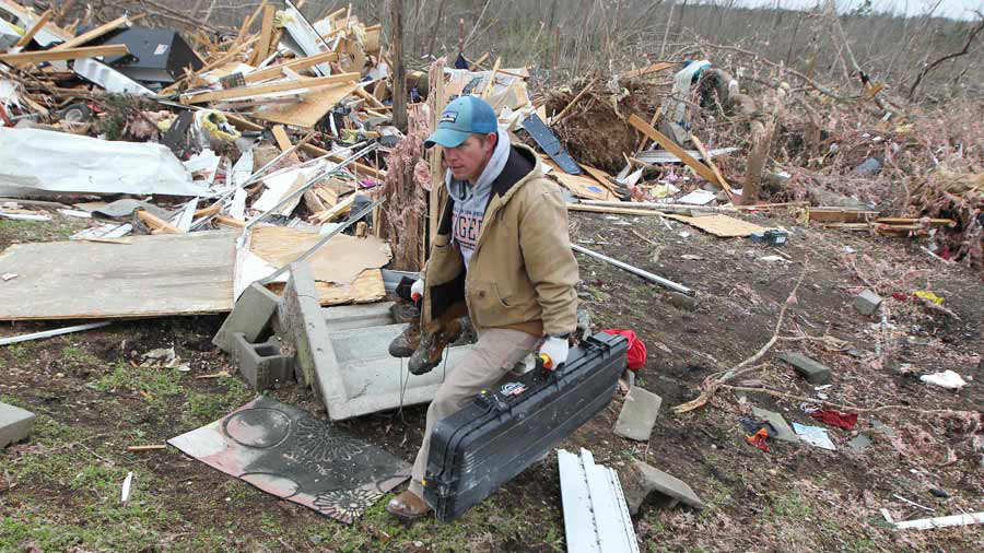 Joey Roush carries items from his mother's home after it was destroye