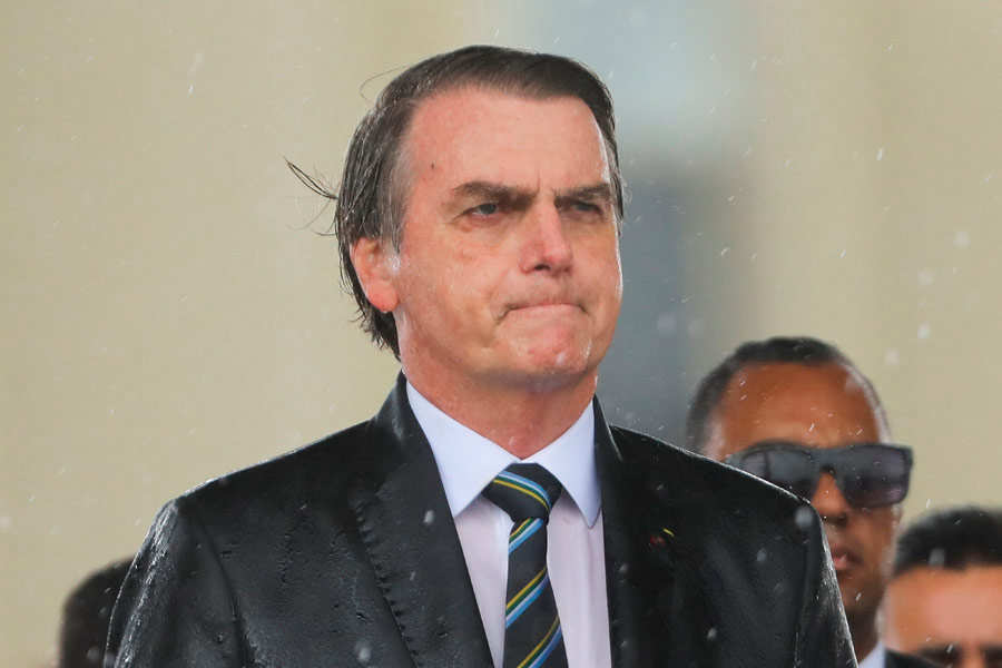 Brazilian President Jair Bolsonaro is drenched with rain during a dow