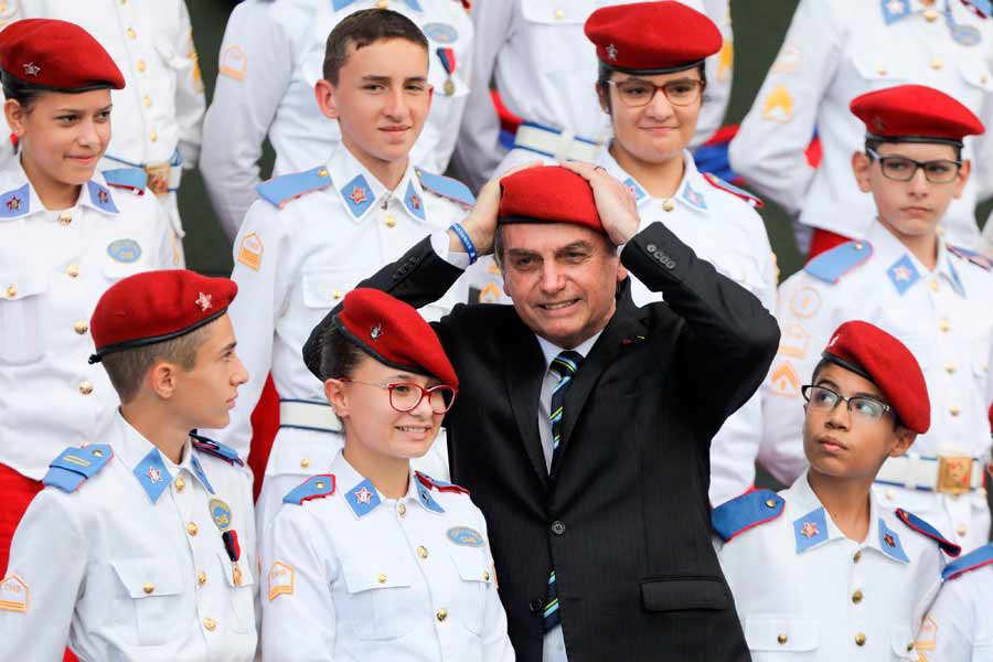Brazilian President Jair Bolsonaro puts a beret on as he poses with s
