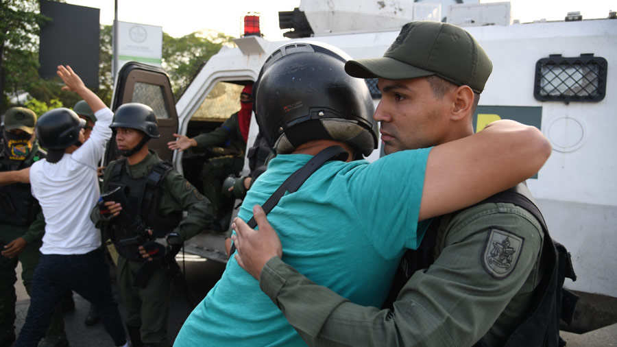 A Venezuelan man hugs a member of the security forces in Caracas on A
